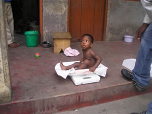 Photo - A nine month old child is weighed at her home
